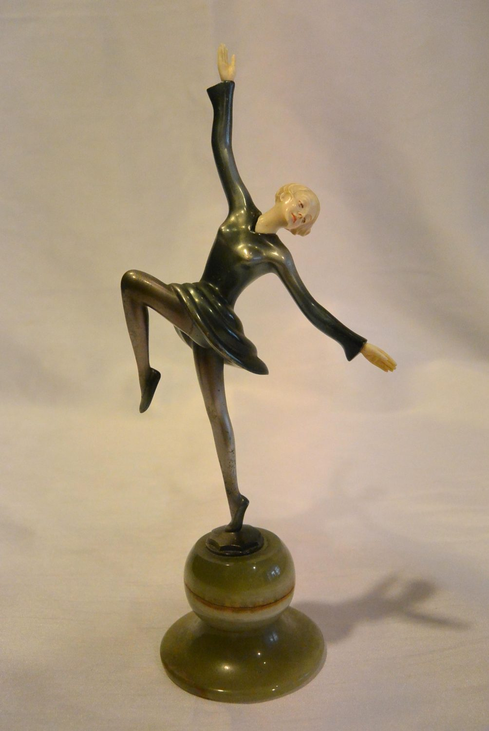 Josef Lorenzl - A cold painted bronze figure of a dancing young lady with ivory cut face and hands, standing on a round onyx socle.